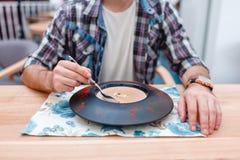 一件格子花呢上衣的一个人在咖啡馆和吃蘑菇奶油汤 特写镜头 免版税库存图片