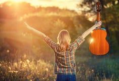 一件格子花呢上衣的女孩在与一把声学吉他的日落 库存图片