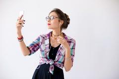一件格子花呢上衣的妇女在plaing与耳机的玻璃 免版税库存图片