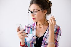 一件格子花呢上衣的妇女在plaing与耳机的玻璃 库存照片