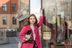 一件桃红色外套的迷人的女孩有一条小狗的 免版税库存照片