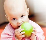 一件桃红色夹克的小婴孩吃绿色苹果 免版税库存图片