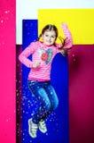 一件桃红色女衬衫和蓝色牛仔裤的一个女孩在她的手上拿着一个糖果并且弹起 库存照片