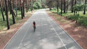 一件桃红色球衣和一件黑盔甲的年轻可爱的嬉戏妇女享受她的在自行车的骑马在夏天森林寄生虫 股票录像