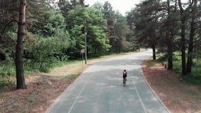 一件桃红色球衣的可爱的少女和黑短裤是放松和享受她的乘驾外面在公园 r 股票视频