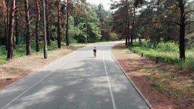 一件桃红色球衣的美丽的年轻嬉戏女孩通过公园循环 后侧方寄生虫视图 影视素材