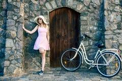 一件桃红色礼服和草帽的女孩在一块织地不很细石头,有一个木门的老墙壁旁边站立 库存照片