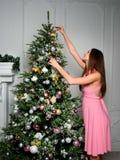 一件桃红色礼服垂悬的玩具的年轻美丽的女孩在圣诞树 免版税库存图片