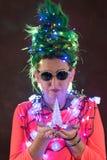 一件桃红色礼服的一个美丽的女孩有绿色头发的装饰了自己与圣诞节诗歌选 她的头发是象圣诞树 的treadled 免版税库存照片