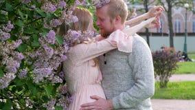 一件桃红色礼服的一孕妇拥抱她的公园的背景的丈夫 等待孩子的年轻家庭 股票视频