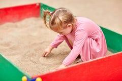 一件桃红色礼服的小女孩在沙盒 库存图片