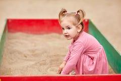 一件桃红色礼服的小女孩在沙盒 免版税库存照片