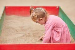 一件桃红色礼服的小女孩在沙盒 免版税库存图片