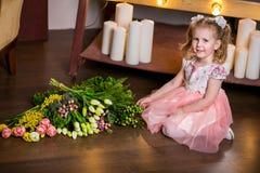 一件桃红色礼服的蓝眼睛的逗人喜爱的女孩坐地板在郁金香、含羞草、莓果和绿叶旁边花束  免版税库存图片