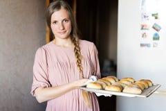 一件桃红色礼服的逗人喜爱的年轻女人有一把大镰刀的在冰箱附近的厨房里 女主人在她的厨房里 一位主妇 库存图片