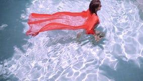一件桃红色长的礼服的女性在一个蓝色水池游泳在水下 桃红色织品在水中开发 股票录像