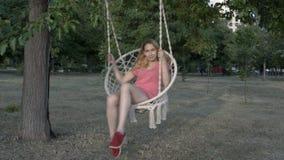 一件桃红色T恤杉的一个年轻十几岁的女孩在垂悬的摇摆摇摆,编织从绳索,在城市公园在日落和微笑 股票录像