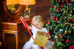 一件欢乐礼服的小女孩打开礼物 库存照片
