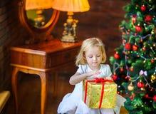 一件欢乐礼服的小女孩打开礼物 免版税库存图片
