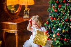 一件欢乐礼服的美丽的小女孩打开礼物 免版税库存图片