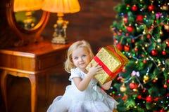 一件欢乐礼服的美丽的小女孩打开礼物 库存图片
