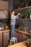 一件毛线衣和牛仔裤立场的少年女孩在凳子和在厨房的上部架子的浇灌的花在晚上 图库摄影