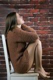 一件毛线衣的女孩在一把木椅子 图库摄影