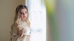 一件毛线衣的美丽的女孩用在窗口附近的茶 股票视频