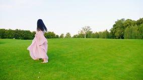 一件浅粉红色的礼服的无忧无虑的孕妇 走通过绿色草甸 股票视频