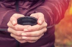 一件淡紫色夹克的一个女孩拿着从一个热水瓶的一块玻璃用热的茶 在秋天公园 库存图片