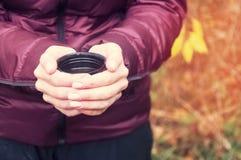 一件淡紫色夹克的一个女孩拿着从一个热水瓶的一块玻璃用热的茶 在秋天公园 库存照片