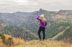 一件淡紫色夹克的一个女孩看入在山的距离,山的看法和一个秋季森林由阴云密布 免版税库存照片