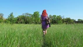 一件淡紫色礼服的红发女孩,有背包和袋子的医药草本通过一个象草的草甸走 股票录像