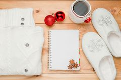 一件温暖的毛线衣、拖鞋和一个笔记本写的愿望 库存图片