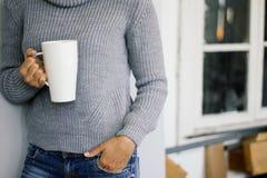一件温暖的灰色毛线衣的一名妇女在她的手上站立在木窗口并且拿着一个白色杯子 偶然的样式 免版税图库摄影