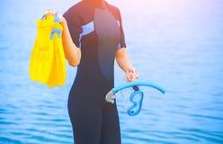 一件潜水衣的一个女孩潜水者拿着与一支蓝色管的一个面具在她的手和黄色飞翅上 库存图片