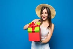 一件激动的逗人喜爱的女孩藏品的画象打开了当前箱子被隔绝在蓝色背景 免版税库存照片