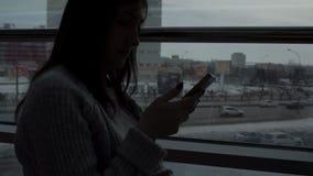 一件灰色毛线衣的女孩有在一个咖啡馆的一个电话的由在特大的城市背景的窗口 股票视频