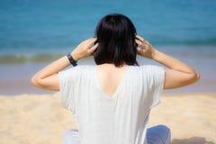 一件灰色礼服佩带的耳机的年轻亚裔妇女,听到音乐在海滩 天空蔚蓝和热带海滩水晶海  免版税库存照片