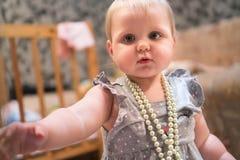 一件灰色礼服的一女孩站立与小珠在她的脖子上 惊奇的金发女孩画象有小珠的 免版税库存图片