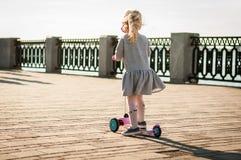 一件灰色礼服的小白肤金发的女孩在路乘坐滑行车 免版税库存图片