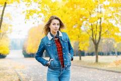 一件牛仔布夹克和牛仔裤的俏丽的女孩在yel背景  免版税图库摄影