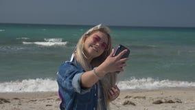 一件牛仔布夹克的年轻白肤金发的妇女在海的背景由在智能手机的视频通话讲她的头发 股票录像