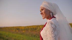 一件白色全国礼服的一美丽的少女在领域和神色站立往日落然后转向凸轮 股票录像