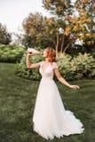 一件白色典雅的婚礼长的礼服的年轻白肤金发的女孩和头发,从a的饮用的香槟华美的卷毛  免版税库存图片