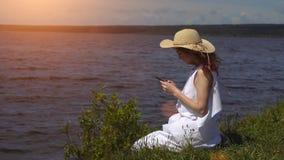 一件白色夏天礼服的美丽的红发女孩使用一个手机坐岸和河 库存图片
