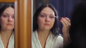 一件白色外套的一年轻女人在镜子前面做与一把化妆刷子的眼睛构成 股票录像