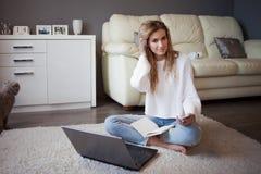 一件白色套头衫和牛仔裤的迷人的女孩坐与笔记本的地板 库存照片