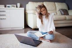 一件白色套头衫和牛仔裤的迷人的女孩坐与笔记本的地板 库存图片