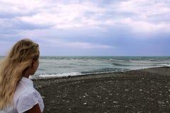 一件白色女衬衫的一个女孩看一场风暴 免版税库存图片